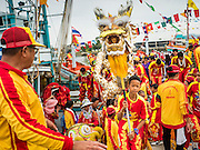 """23 JUNE 2015 - MAHACHAI, SAMUT SAKHON, THAILAND: Chinese dragon dancers get off a fishing boat during the procession for the City Pillar Shrine in Mahachai. The Chaopho Lak Mueang Procession (City Pillar Shrine Procession) is a religious festival that takes place in June in front of city hall in Mahachai. The """"Chaopho Lak Mueang"""" is  placed on a fishing boat and taken across the Tha Chin River from Talat Maha Chai to Tha Chalom in the area of Wat Suwannaram and then paraded through the community before returning to the temple in Mahachai.   PHOTO BY JACK KURTZ"""