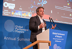 © Licensed to London News Pictures. 22/10/2018. Bristol, UK. Global Parliament of Mayors Annual Summit, 21-23 October 2018, at Bristol City Hall. Picture of ROBERT MUGGAH, global topic expert on data on refugees and migration, addressing the conference. The Global Parliament of Mayors 2018 is the biggest and most ambitious Annual Summit to date. GPM Bristol 2018 will host up to 100 global mayors for an action-focused summit that addresses some of the biggest challenges facing today's world cities. GPM Bristol 2018's theme, Empowering Cities as Drivers of Change, will focus minds on global governance and the urgent need for the influence, expertise and leadership of cities to be felt as international policy is shaped. GPM Bristol 2018 will provide mayoral delegates with a global network of connections and a space to develop the collective city voice necessary to drive positive change. The programme will engage participants in decision-making, with panels, debate and voting on priority issues including migration and inclusion, urban security and health, and is a unique chance to influence decisions on the most pressing issues of our time. Photo credit: Simon Chapman/LNP