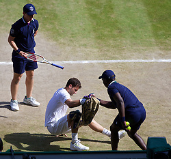 LONDON, ENGLAND - Friday, July 4, 2014: Grigor Dimitrov (BUL) is helped up by a ball-boy during the Gentlemen's Singles Semi-Final match on day eleven of the Wimbledon Lawn Tennis Championships at the All England Lawn Tennis and Croquet Club. (Pic by David Rawcliffe/Propaganda)