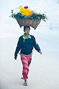 Woman walking from morning market in fog, Burma