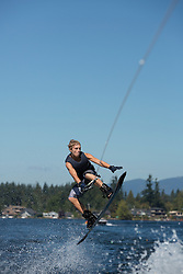 United States, Washington, Lake Sawyer, teen boy doing a wakeboarding jump.  MR