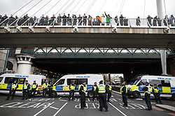 © Licensed to London News Pictures . 01/04/2017 . London , UK . Police detain pedestrians on the Golden Jubilee Bridge on Victoria Embankment whilst the demonstrations pass along Victoria Embankment below . The EDL and Britain First both hold demonstrations in London , opposed by anti-fascist groups , including Unite Against Fascism . Photo credit : Joel Goodman/LNP