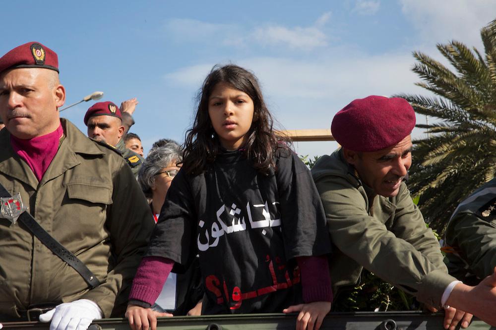 """La fille ainé de Chokri Belaid sur le jeep qui transporte le corps de son père, sur son t-shirt est ecrit """"Pappa qui l'a tué"""""""