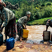 The water from the river that 25 year old Tesomech (in the middle) goes to is also not safe. In order to supply her eight-member family with water, Tesomech must carry a 35 litre container twice a day for four hours. She suffers from frequent backaches. Gurage, Ethiopia.