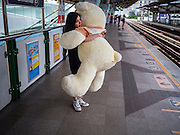 22 SEPTEMBER 2015 - BANGKOK, THAILAND:  A woman on the Sukhmvit Skytrain line with a large stuffed teddy bear.     PHOTO BY JACK KURTZ