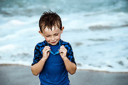 Young boy with goggles at the beach.