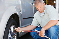 Man Filling Tires on RV