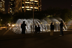Stock photo of people standing around Discovery Green's fountains at night