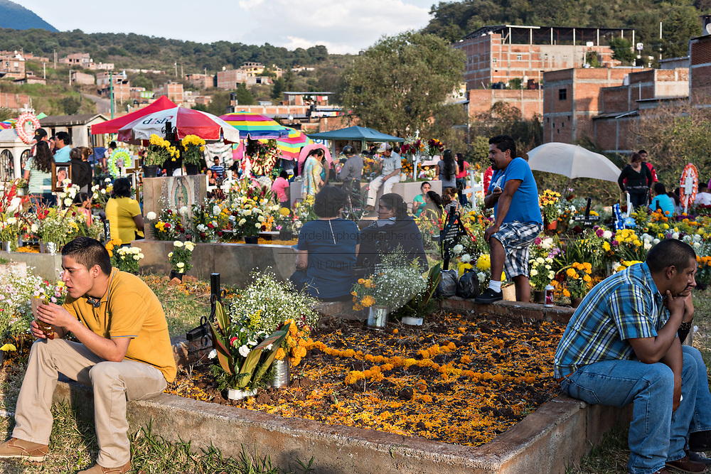 Family members enjoy a picnic at the gravesite of relatives as they celebrate the Day of the Dead festival November 2, 2017 in Quiroga, Michoacan, Mexico.  The festival has been celebrated since the Aztec empire celebrates ancestors and deceased loved ones.