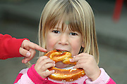 little girl eating a piece of bread with her sister pointing at it