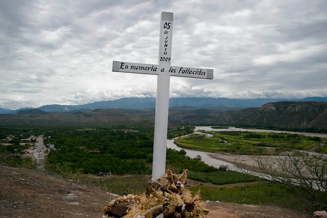 "A cross remember the peoples who dies at the ""La curva del diablo"", devils curves near to Bagua, Amazonas, Peru. After the events of June 5 in the Amazonian province of Bagua, in northeastern Peru, where 24 policemen and a number still not confirmed of natives from the communities of the ÒAlto Mara-onÓ and civilians died in clashes after a series of demonstrations in opposition to the approval by the Peruvian government, for a group of ordinances that allow large flexibility in the restrictions on resource extraction in the area, breaking the 169 agreement of ILO (International Labour Organization), which requires the consultation of indigenous communities about the exploitation of nature in their territories. One of the most active communities was the awajun, a warlike and revengeful people, heritors of the Jibaros and recently contacted near to 1950. For the leader or ""apu"" for one of the aguarunas riverside communities of the Mara-on, Simon Weepiu, Òthe force of this movement come from the conviction of the struggle, which is caused by the ancestral development as based on worldview, which provides the native of a special power, that of becoming one with his idea and his brothers, to focus all on the same objective and be just a great strength."" The government aims to generate development in the area allowing the exploitation of property, The jungle is rich in gold and oil, and even argue that natural wealth of the region belong to all Peruvians, and not just the communities that inhabit it, but acts as the oil«s filtration to waters of the Mara-on, left in evidence that in a complex ecosystem like jungle that mixed spilled oil by rain in the river, home to fishes, as well as the waters that irrigate cassava, bananas, sugarcane and other elements vital to the development of communities. The natives, insist that the forest is not only home, is where they get medicines to cure their sick and food for their families. The pre-existence and natural wisdom places them"