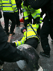 © under license to London News Pictures. 9/12/2010. An unconscious policeman is dragged to safety by colleagues. On the day that MPs vote on tuition fees, 1000s demonstrated in London against a proposed rise in fees and cuts in support. Photo credit should read Fuat Akyuz/London News Picture