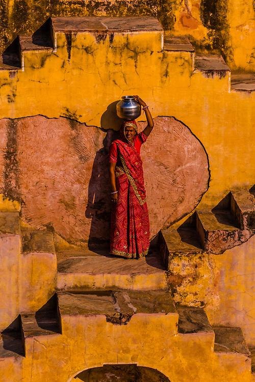 A local woman going to fetch water in Panna Meena Ka Kund step well, (baori), Amer (near Jaipur), Rajasthan, India.