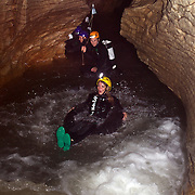 Participants on black water tubing while Black Water rafting in the Waitomo Glowworm Caves, Waitomo, North Island, New Zealand..The Legendary Black Water Rafting Company is New Zealand's first black water adventure tour operator which takes tourists through the  Ruakuri Cave at Waitomo..The five hour expedition combines abseiling the 35 metre entrance. climbing, a flying fox. black water tubing, leaping and floating through Ruakuri Cave and observing glow worms. The journey concludes  into the sunlight of the Waitomo forest..Waitomo, New Zealand,, 14th December  2010 Photo Tim Clayton