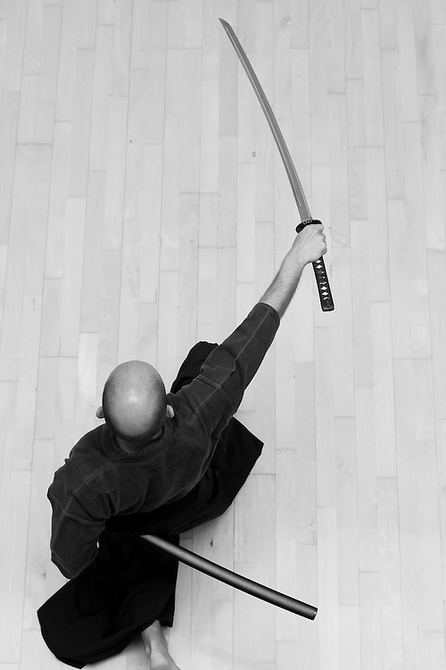 Seen from above, a Iaido practicioner does a horizontal cut, in the beggining of a kata