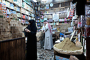 A black-veiled woman examines bars of olive oil soap in Aleppo's suq