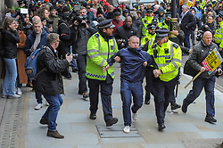 A man was led away by police during an anti racism march in support of UN anti racism day. The march was organised by the campaign group Stand up to Racism. Westminster, London, 16th March 2019.