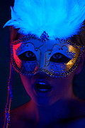 Portrait of a young woman with a surprised expression wearing a mask.Black light