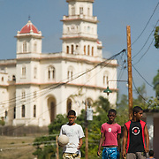 Boys walk down a street near the basilica of El Cobre, Cuba on Wednesday July 9, 2008.