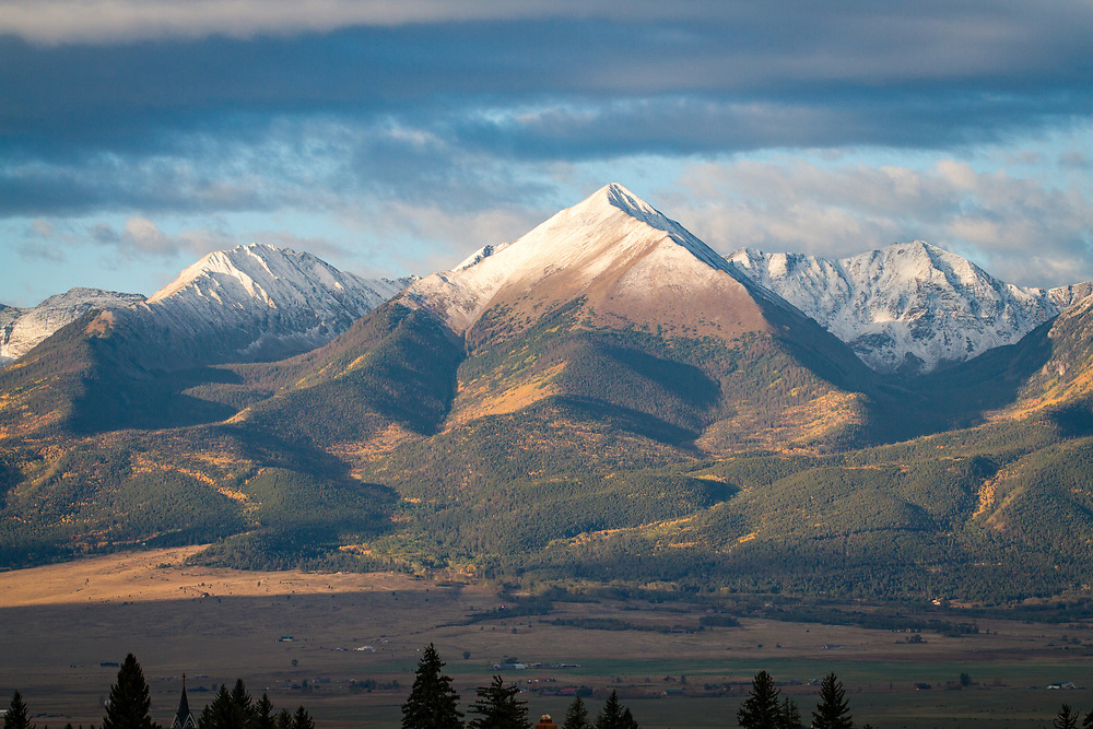 Horn Peak stands over Westcliffe, topped with an early snow and streaked with fall color.