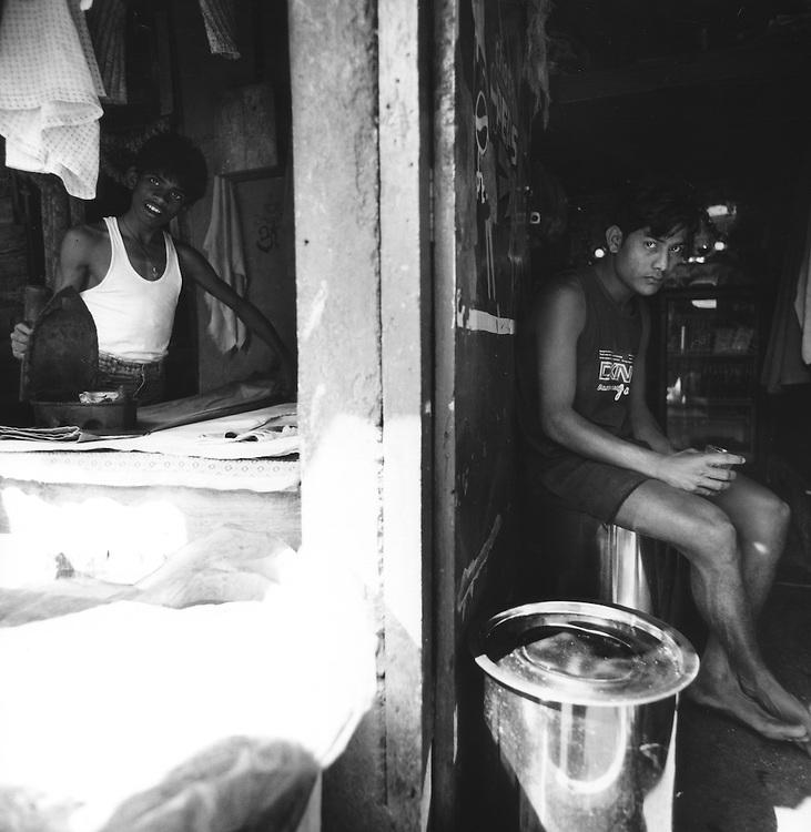 Giovane lavandaio dobhi mentre stira, altro in pausa in un piccolo bar della lavanderia.<br /> <br /> Young Dhobi washerman while stretch, another pause in a small bar of laundry.