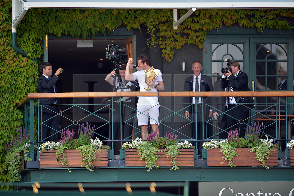 © London News Pictures. 07/07/2013 . London, UK. Andy Murray holding the trophy as he celebrates  on the clubhouse balcony after his men's singles final victory over Novak Djokovic of Serbia at the Wimbledon Lawn Tennis Championships final, becoming the first male to win the tournament in 77 years. Photo credit: Mike King/LNP