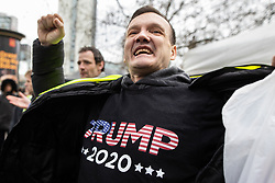 "© Licensed to London News Pictures . 09/02/2019. Manchester , UK . A man flashes a TRUMP 2020 shirt at anti-fascists during a "" Yellow Vest "" protest in Manchester City Centre . The yellow vest concept has been adopted from French demonstrators by some British groups in support of Brexit , Donald Trump and former EDL leader Stephen Yaxley-Lennon - aka Tommy Robinson . A similar demonstration in the city in January was ridiculed after protesters were kettled by police in front of a branch of Greggs the Baker . Photo credit : Joel Goodman/LNP"