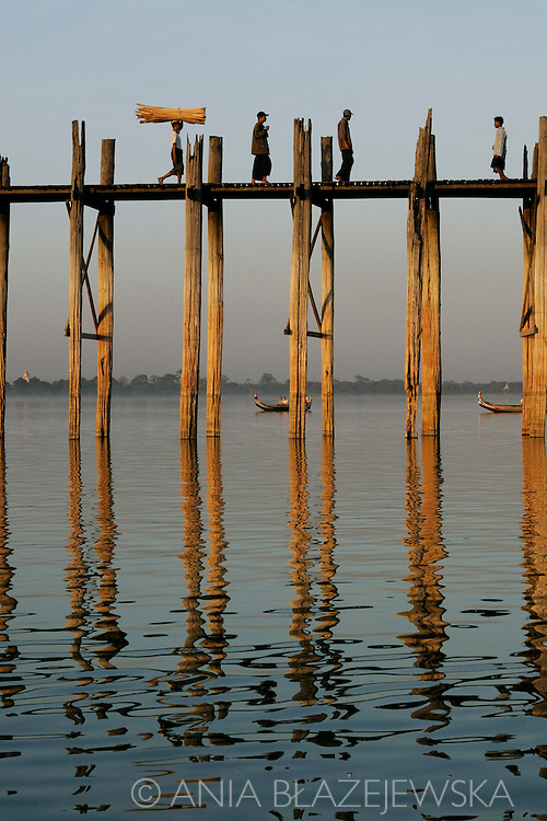 Burma/Myanmar, Amarapura. People crossing U Bein's bridge - one of the most popular tourist destination in Myanmar.