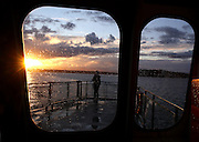 A ferry passenger watches the sunset while riding on the ferry from Southworth to Fauntleroy during a stormy September evening. <br />