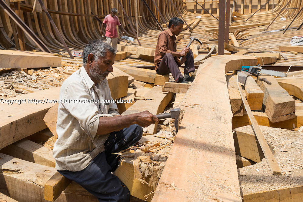 Craftsmen building a traditional wooden dhow cargo ship in shipyard beside The Creek River in Dubai United Arab Emirates