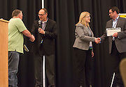 Amy Taylor-Bianco, middle-right, an associate professor in the management systems department in Ohio University's College of Business, and Tim Reynolds, the director of the Robert D. Walter Center for Strategic Leadership, middle-left, present license plates to graduate students David Felty, left, and Timothy Holmes, right, during the College of Business Center for Leadership Event in Baker Ballroom on April 24, 2016.