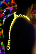 Silhouette of a man with a glowing yellow chain around his neck against a colorful background.Black light