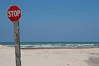 Stop sign at end of the road at Boca Chica, mouth of the Rio Grande/Rio Bravo River between Texas, USA and Tamaulipas, Mexico.