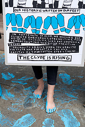 Glasgow, Scotland, UK. 21 March, 2019. A  'Blue Wave' demonstration by the Extinction Rebellion climate change protest group saw protesters make blue footprints, made from water-soluble paint, across George Square to the City Chambers. The peaceful protest briefly held up traffic. The Group aims to highlight threat of rising water levels in the River Clyde and of global climate change.