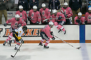 Pittsford forward John Mozrall is pursued by McQuaid defenseman Conner Adami during the annual Pink the Rink game at RIT's Gene Polisseni Center in Henrietta on Saturday, February 4, 2017.
