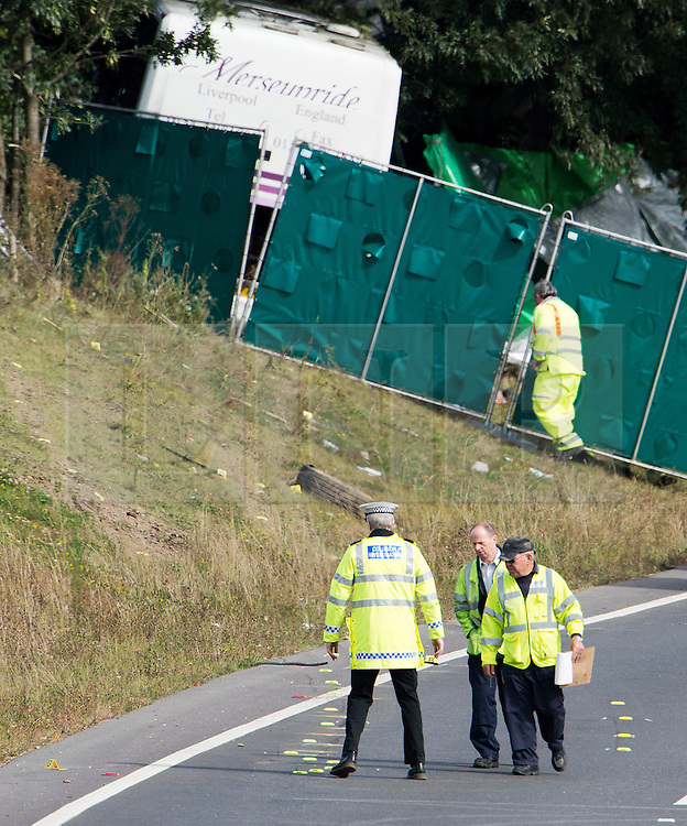 © London News Pictures. 11/09/2012. Hindhead, UK . A police officer examining evidence markers and skid marks (foreground) at the scene of a fatal bus crash on the north bound A3 motorway near Hindhead Tunnel, Hindhead, Surrey on September 11, 2012.Three people were killed and a number of others seriously injured when a coach carrying overturned after crashing into a tree. Photo credit: Ben Cawthra/LNP