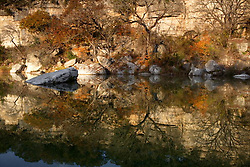 Stock photo of a colorful fall landscape reflection in the Guadalupe river in the Texas Hill Country