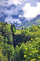 Ticino, Southern Switzerland. In the foreground, a waterfall cascading into a gorge.  The backdrop is the imposing Swiss Alps along the Italian border.