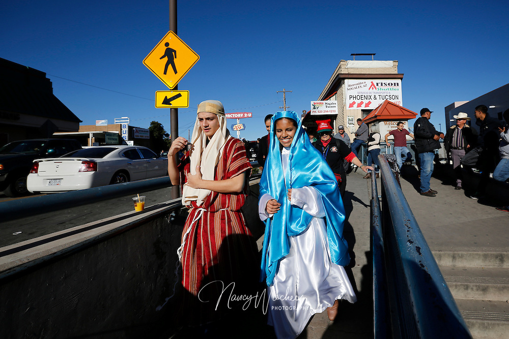 "Catholic high school students Saul Gonzalez and Kenia Salas, dressed  as Joseph and Mary, make their way to the DeConcini Port of Entry along the Arizona-Sonora border in Nogales, Arizona, Dec. 20. Students from Salpointe and Lourdes Catholic high schools in Arizona, led a bi-national ""posada"" recalling Mary and Joseph's search for shelter before the birth of Christ. The annual event held by  the Kino Border Initiative and Dioceses Without Borders reflected on the struggles of migrants and migrant families. (CNS photo/Nancy Wiechec)"