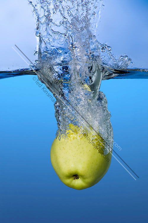 An apple is dropped in water, creating a splash.