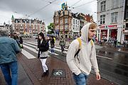 Voetgangers steken het Muntplein in Amsterdam over.<br /> <br /> Pedestrians cross the street at the Munt Square in Amsterdam.