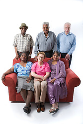 Multiracial group of older people sitting on a sofa together smiling,