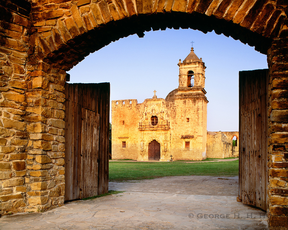 0506-1007B ~ Copyright: George H. H. Huey ~ Church of San Jose y San Miguel de Aguayo, at sunset, through mission wall doors. Church construction began 1720. San Antonio Missions National Historical Park, Texas.