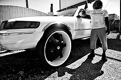 Bruce Davis, 35, of North Philadelphia stands next to a former Police Intercepter, a 1998 Mercury Grand Marquis he named White Panda that stands on 30 inch tall wheels, as members of the local classic and American muscle car community gather for a meet on a North Philadelphia, on September 15, 2019.