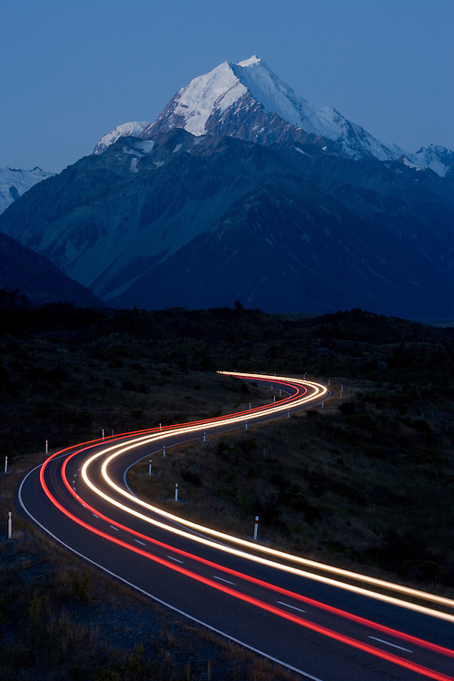 New Zealand, South Island, Aoraki Mount Cook National Park, Blurred traffic lights from car headlights driving on winding country road toward Mount Cook in Southern Alps on clear summer night