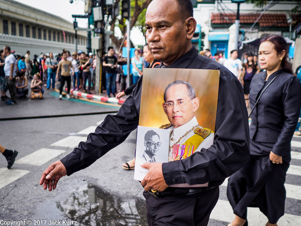 26 FEBRUARY 2017 - BANGKOK, THAILAND:  A man holding portraits of Bhumibol Adulyadej, the Late King of Thailand, walks into the Grand Palace to pay respects to the revered monarch. Thousands of Thais continue to line up at the Grand Palace in Bangkok daily to pay respects to Bhumibol Adulyadej, the Late King of Thailand, who died on 13 October 2016. The government set a year long mourning period for the revered King, who will be cremated in late 2017.       PHOTO BY JACK KURTZ