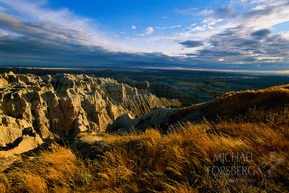 "Badlands National Park, South Dakota. Rising abruptly from the prairie hills of southwestern South Dakota, ""The Wall"" is the defining topographical feature of Badlands National Park. Once a lush marshy plain, this spectacular park was form by millions of years of being ravaged by wind and water. Filled with rocky spired, steep canyons, low slung buttes, and jagged ridges, Badlands National Park covers 244,000 acres and contains one of the worlds richest deposits of fossils from the Oligocene epoch."