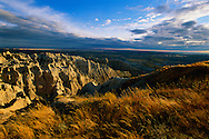 """Badlands National Park, South Dakota. Rising abruptly from the prairie hills of southwestern South Dakota, """"The Wall"""" is the defining topographical feature of Badlands National Park. Once a lush marshy plain, this spectacular park was form by millions of years of being ravaged by wind and water. Filled with rocky spired, steep canyons, low slung buttes, and jagged ridges, Badlands National Park covers 244,000 acres and contains one of the worlds richest deposits of fossils from the Oligocene epoch."""