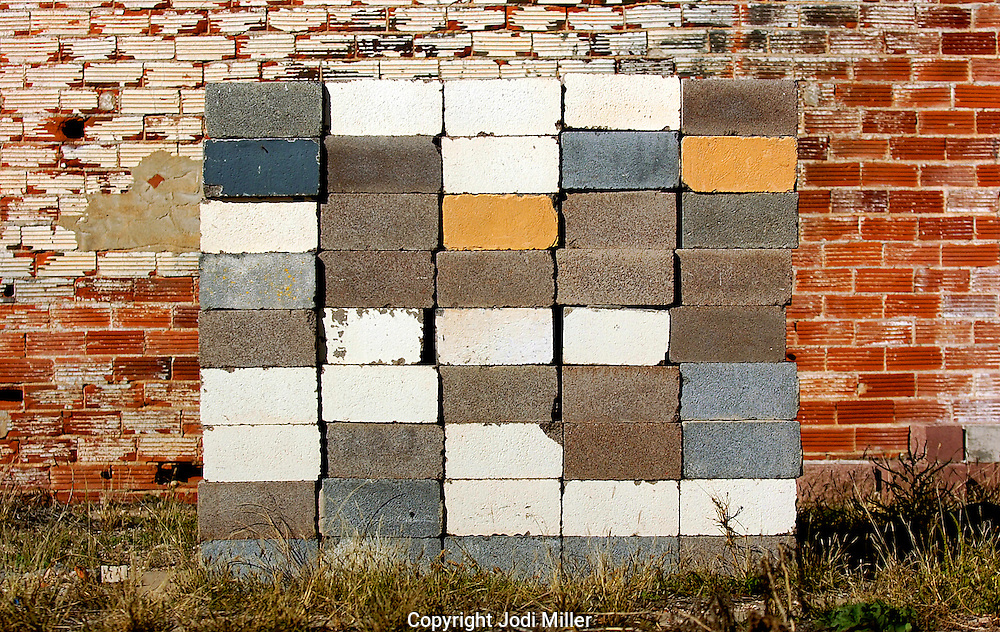 Stacks of cinder blocks and building materials in front of a brick wall.