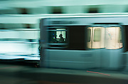 Image of a Washington, D.C. metro train and conductor speeding past a metro station.